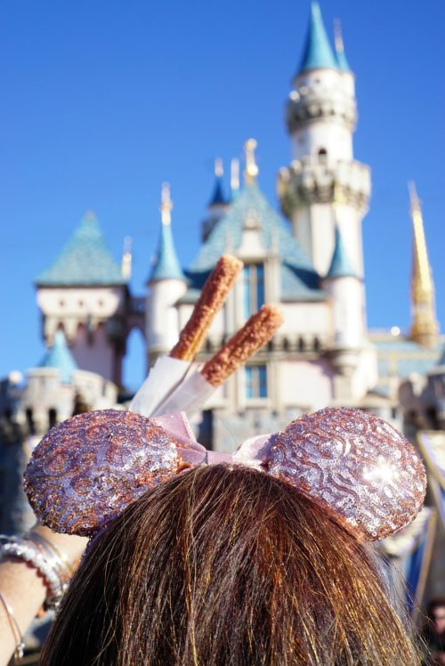 Rose Gold Ears and Rose Gold churros in front of Disneyland castle